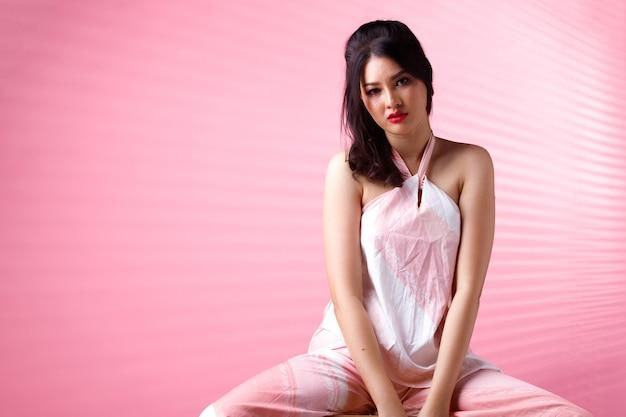 ファッションビューティーウーマンは黒髪で悲しそうな泣き声を表現しています。アジアの女の子の肖像画はピンクのトーンの壁にピンクのドレスを着て、スツールの椅子に座って、スペースをコピーします