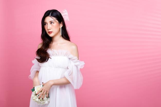 Fashion beauty woman имеет черные волосы, выражающие гнев. азиатская девушка носит розовое платье поверх стены розового тона, держит цветок и пытается примириться с парнем, скопируйте пространство