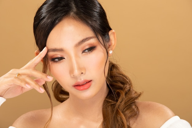 ファッションビューティーウーマンは長い黒のブロンドの髪をしていて、幸せな気持ちを表現しています。アジアの女の子の肖像画は黄色のトーンの壁、コピースペースに白いドレスを着ています