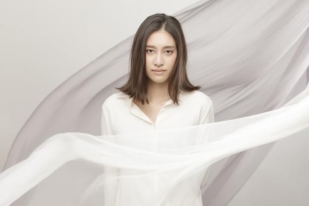 ファッションビューティーウーマンはストレートの黒髪が短く、表情豊かです。アジアのタイの女の子の肖像画は風に布の波と白いシャツを着て、オフホワイトの背景の上に空に羽ばたき生地を投げる
