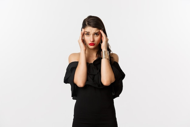 Fashion and beauty. young modern woman in glamour dress, jewelry and makeup, touching head and looking exhausted, feeling dizzy, standing over white background.