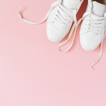 Fashion blog look. white womens sneakers on pink background. flat lay, top view