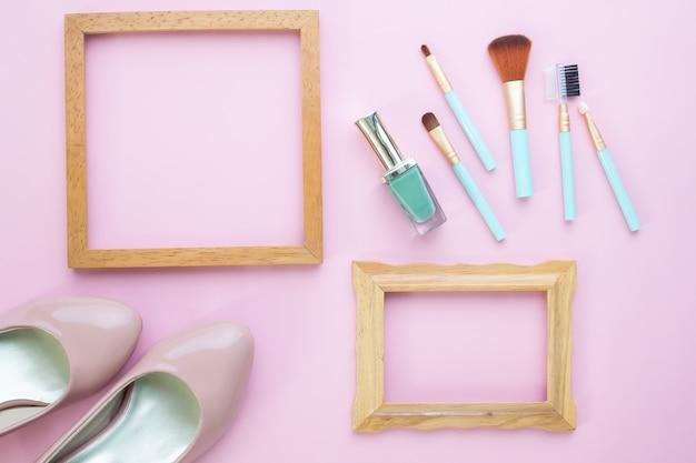 Мода блоггер концепции с деревянными рамами, набор кисти и обувь на розовом фоне