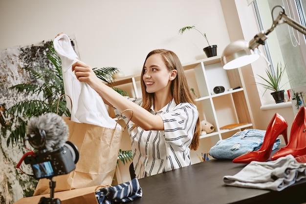 새로운 것을 녹음하는 동안 카메라에 새 흰색 셔츠를 보여주는 패션 블로거 행복하고 귀여운 여성
