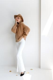 灰色の背景に秋の服を着たファッションブロガー。買い物