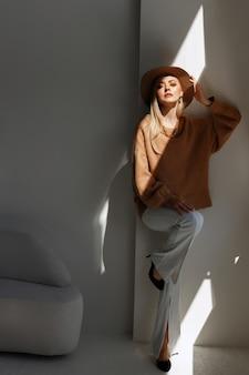 光の中で明るいスタジオでスタイリッシュな服を着たファッションブロガー