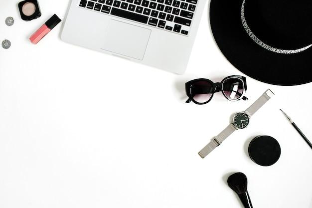 Офисный стол модного блоггера с ноутбуком и стильной женской коллекцией аксессуаров на белом
