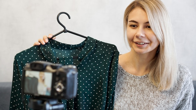 Fashion blogger recording video for blog. woman in front of the camera holding a green dress in her hands. close up portrait