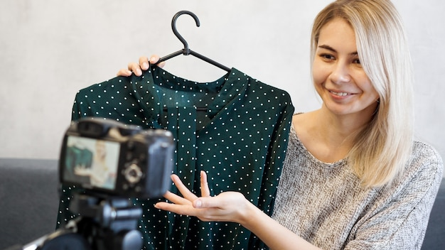 Fashion blogger recording video for blog. woman in front of the camera holding a green dress in her hands