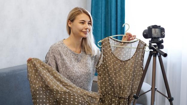 ブログのファッションブロガー録画ビデオ。ベージュのドレスを手に持っているカメラの前の女性
