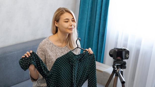 Модный блогер записывает видео для блога. женщина перед камерой, держа в руках зеленое платье