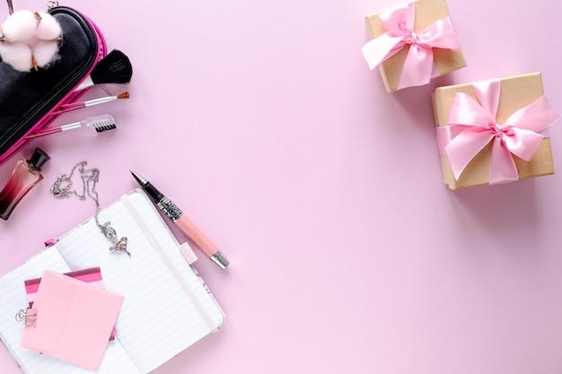 Мода блоггер рабочее пространство с ноутбуком и женский аксессуар, косметические продукты на розовом столе.