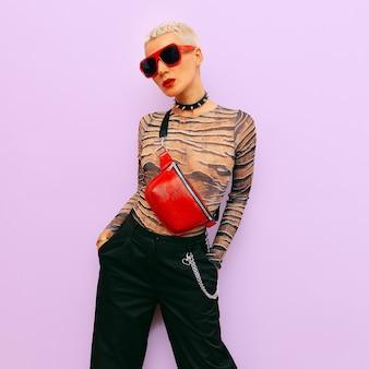 ファッションブロンドレディスワッグラグジュアリースタイル。スタイリッシュなアクセサリー。クラッチとサングラス