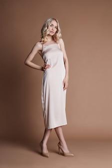 Fashion blonde in a long beautiful dress posing