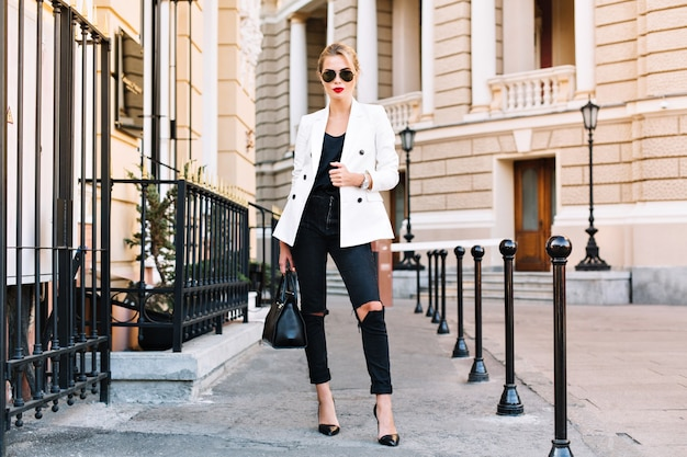 Fashion blonde woman in sunglasses is walking on street on high heels. she wears white jacket and black ripped jeans.