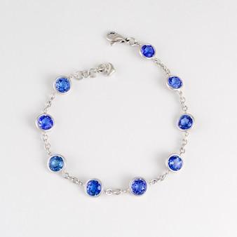 Модный браслет из синего сапфира на белом фоне