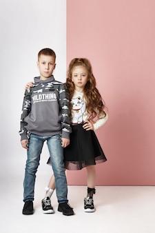 컬러 벽에 세련 된 옷을 입고 패션 소년과 소녀. 어린이에 가을 밝은 옷, 컬러 퍼플 핑크 벽에 포즈 아이.