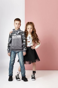 Fashion boy and girl in stylish clothes on colored wall. autumn bright clothes on children, a child posing on a colored purple pink wall.