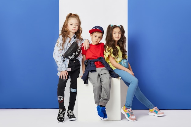 Fashion boy and girl stylish clothes colored wall