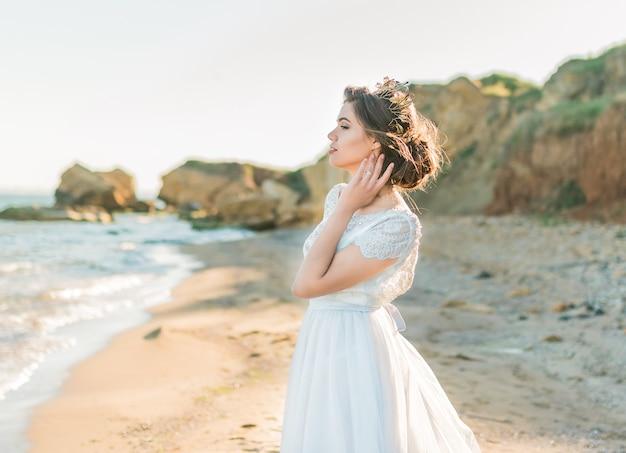 바다 또는 바다 해안에 고급 웨딩 드레스의 패션 신부 모델