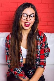 Фасонируйте яркий портрет молодой женщины с удивительными длинными волосами и ярким макияжем, весело проводя время и показывая язык в комнате, нося хипстерский наряд и очки.