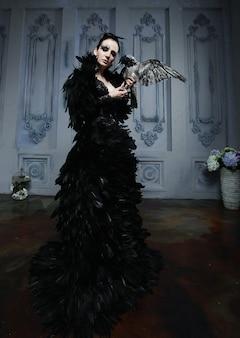 大きな鳥を保持している黒いドレスのファッションブルネットモデル