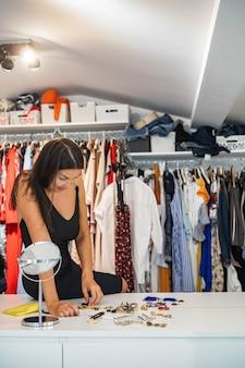 Модная брюнетка женщина, выбирающая аксессуары, готовится к вечеринке в домашнем гардеробе