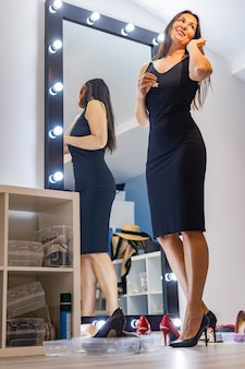 Fashion brunette woman choosing earrings looking at mirror getting ready to party event