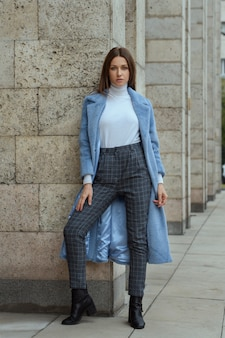 Fashion brunette woman female model in opened blue coat with white jacket and grey checkered trousers and black boots posing for camera standing near building stone columns on the city street alley