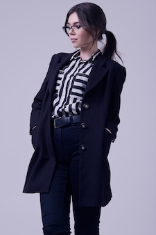 Fashion brunette woman wearing a striped blouse and black jacket