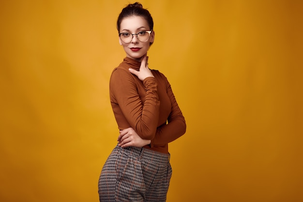 Fashion brunette woman wearing turtleneck and glasses on yellow background