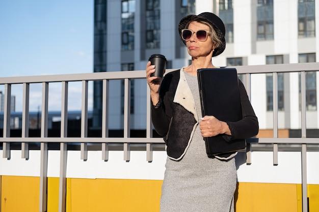 도시에서 커피와 노트북 선글라스와 검은 재킷과 모자에 패션 비즈니스 수석 매력적인 여자
