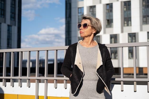 도시에서 선글라스와 검은 재킷에 패션 비즈니스 수석 매력적인 여자