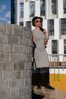 도시에서 드레스와 검은 모자에 선글라스 패션 비즈니스 수석 매력적인 여자