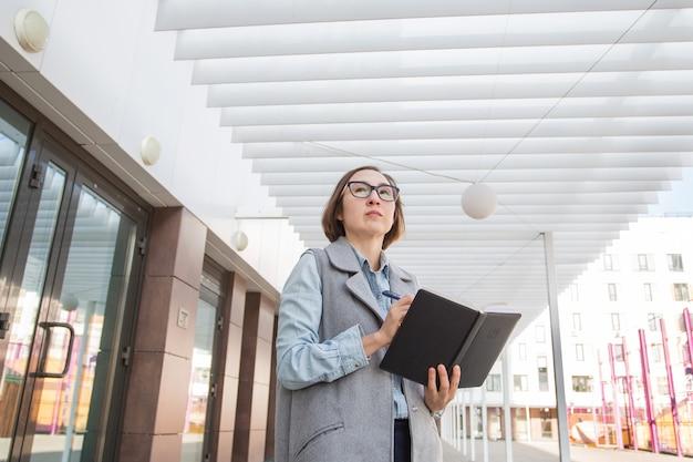 노트북을 들고 안경 패션 비즈니스 여자입니다. 가을 도시에 서십시오.