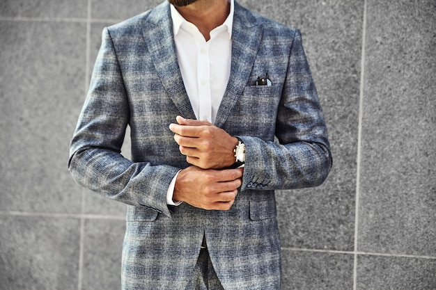 Fashion businessman model dressed in elegant checkered suit posing near gray wall on street background. metrosexual with luxury watch on wrist