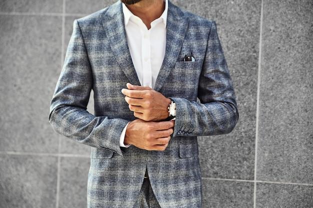 通りの背景に灰色の壁に近いポーズエレガントな市松模様のスーツに身を包んだファッション実業家モデル。手首に高級時計とメトロセクシャル