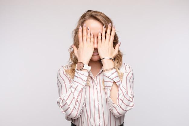 Фасонируйте вскользь бизнес-леди представляя закрывающее лицо рукой изолированное на белой стене студии