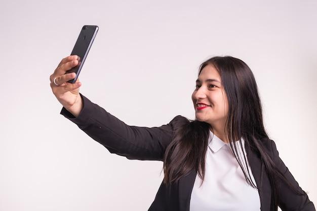 패션, 캐주얼, 현대 및 사람들 개념-스튜디오에서 포즈 젊은 아름 다운 유행 갈색 머리 소녀, 매력적인 여자는 흰색에 selfie를 만든다.