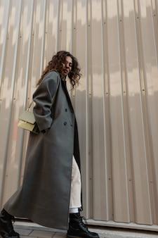 긴 코트에 가방을 든 아름다운 곱슬머리를 한 패션 캐주얼 여성은 금속 벽 근처의 거리를 걷습니다. 여성 도시 스타일과 아름다움