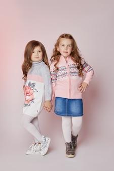 Мода детей две молодые модели девочек дети ставят на розовом фоне. рыжеволосая девушка улыбается, ухаживает за ребенком и косметикой для макияжа