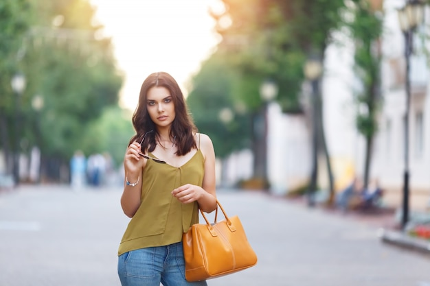 Fashion city portrait of stylish hipster womanwith bag, natural dress, makeup, long brunette hairs, walking alone at weekend, enjoy vacation in europe