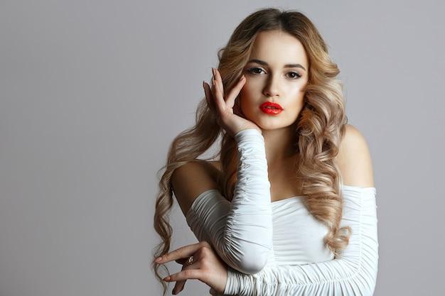 長いウェーブのかかった髪とスモーキーな目のメイクでエレガントな若い女性のファッションクローズアップの肖像画。スタジオは灰色の背景の上で撮影しました。テキスト用のスペース
