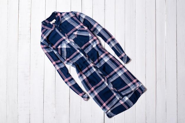 ファッション服。白い木の床の板に青い市松模様のロング シャツ