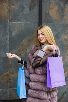 Fashion clothes. fur coat. stylish woman with shopping bags posing on abstract background