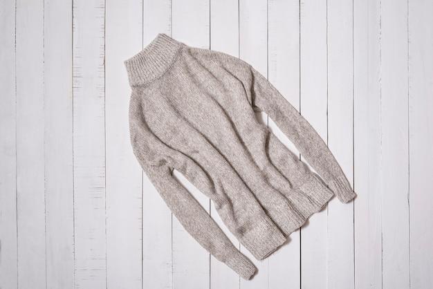 패션 의류. 흰색 나무 바닥 판자에 회색 니트 스웨터