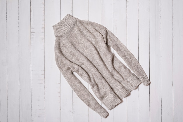Fashion clothes. gray knitted sweater on white wooden floor planks