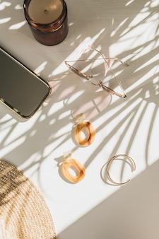 葉の影と白いテーブルの上の女性のアクセサリーとファッションの構成。イヤリング、ブレスレット、サングラス、白地に麦わら帽子