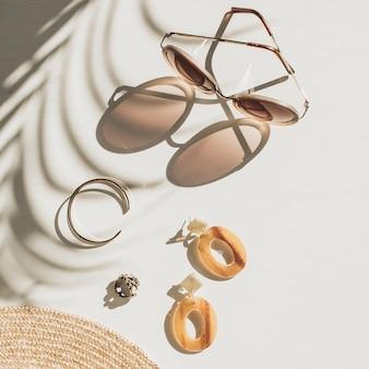 白地にレディースアクセサリーを配したファッションコンポジション。イヤリング、サングラス、ブレスレット、白地に麦わら帽子