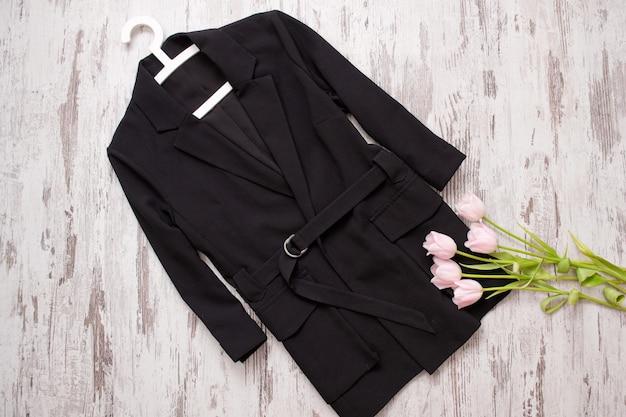 ファッション コンセプト。黒のコート ハンガーとピンクのチューリップ。トップ ビュー、ライト ウッドの背景